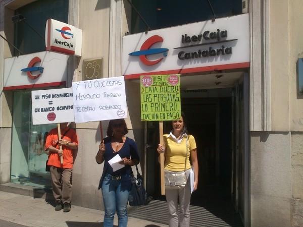 Miembros de la PAH de Cantabria en la puerta de la oficina de Ibercaja que ha sido ocupada por la plataforma
