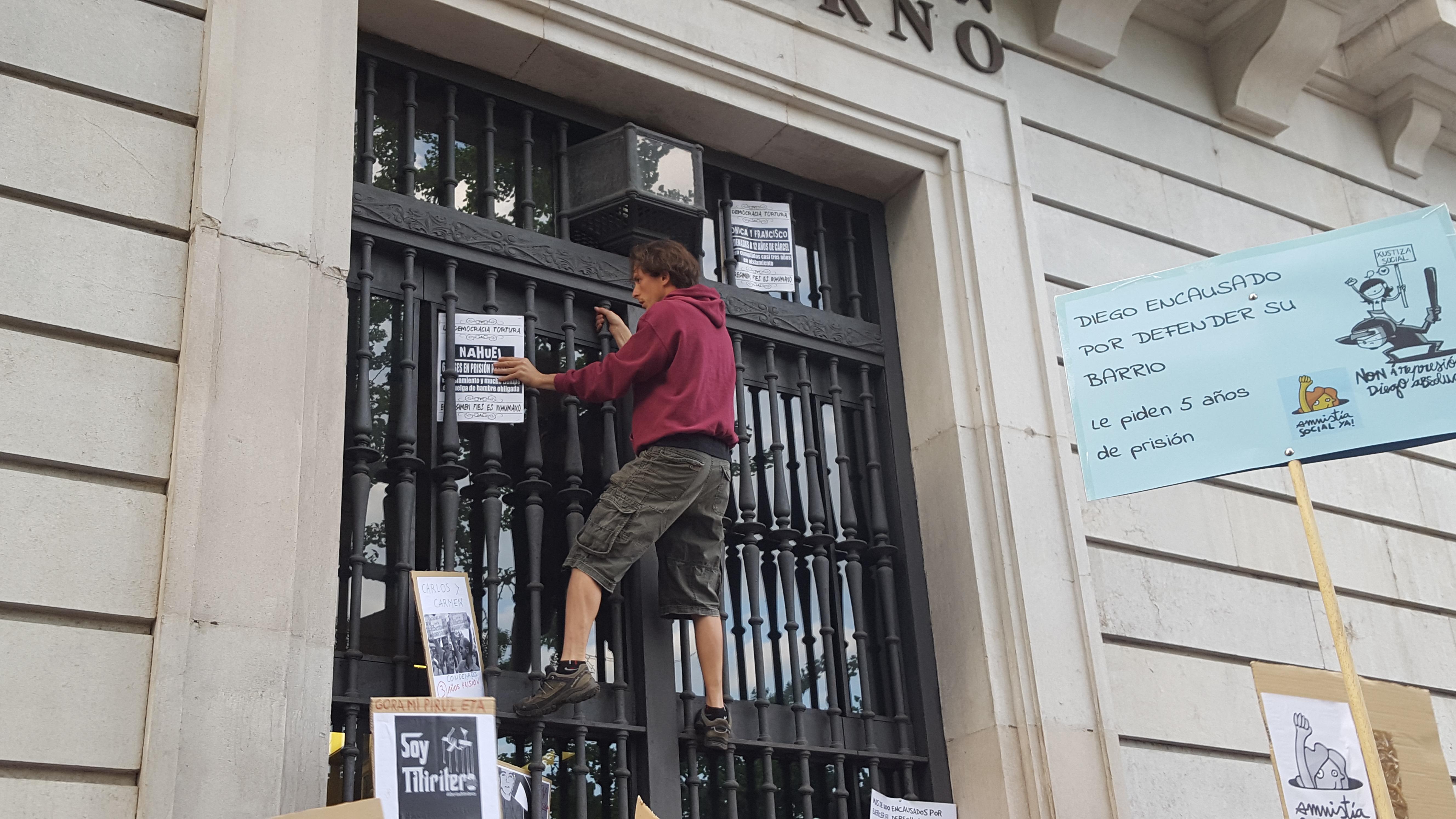 El joven identificado colocando pancartas en el edificio.