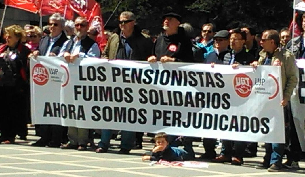 Un niño en el Primero de Mayo bajo la pancarta de los pensionistas