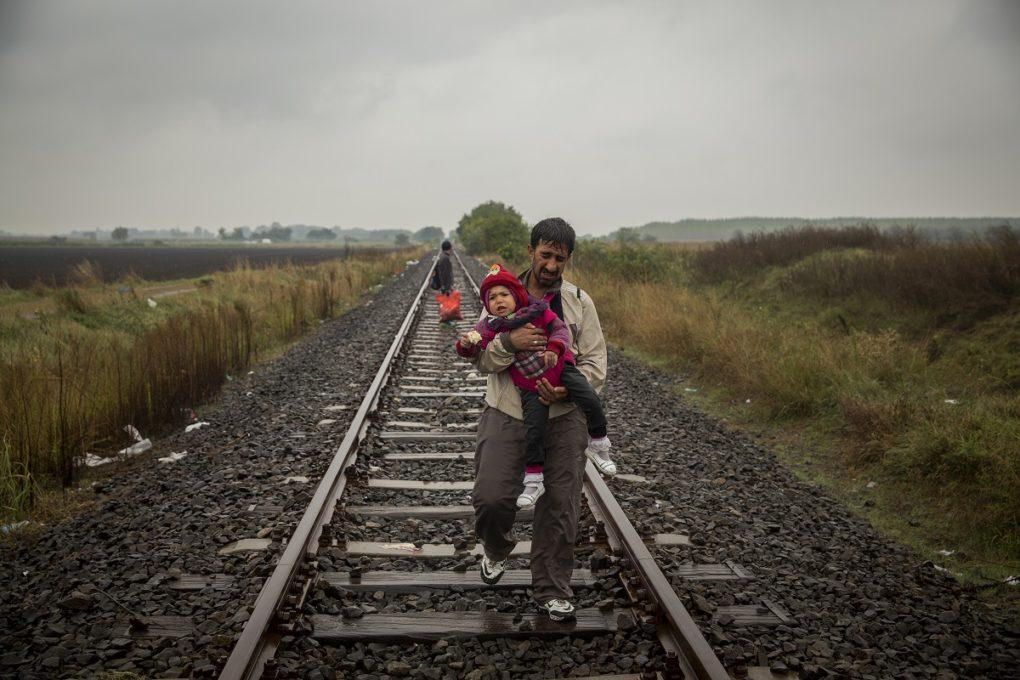 Un padre camina por las vias del tren llevando a su hijo en brazos unos cientos de metros despues de haber cruzado la frontera entre Serbia y Hungria entrando en la localidad de Roszke. Roszke. Hungria.  Olmo Calvo. (10/09/2015)